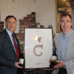 Julius Angelini, Owner, Angelini Wine with Paul Cullen, CT Sales Manager, Angelini Wine, standing beside framed artwork of an art deco Livon Wine label.