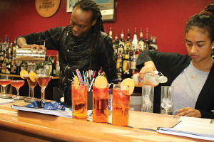 Derrick Edmondson with classmate Naomi Robinson mixing cocktails during class practices.