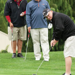 Joe O'Loughlin of Wells Fargo Bank (left) and Richard Beretta of Adler, Pollack and Sheehan (middle) watch Jon Sachs of Adler, Pollack and Sheehan make a putt.