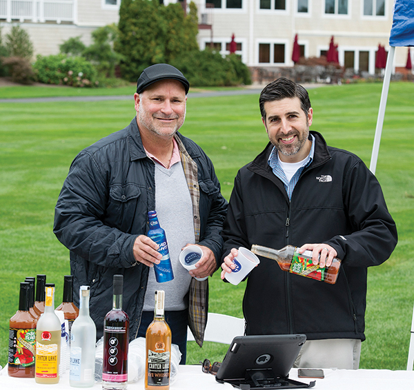 John Richard and David Mangiantine of McLaughlin & Moran's Elevated Spirits Division prepared tasting samples at one of the holes.