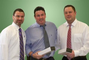 Frank Latorra, Sales Manager at Hartley and Parker, presents Brian Martin and John Hellman, both sales reps, with watches for their 10 year anniversaries.