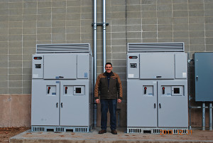 Tom Troiano, warehouse manager of Allan S. Goodman helped overse the installation. He is shown standing between the system's two inverters. Solar inverters convert the panel output into useable electricity.