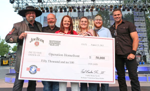 """Country duo Montgomery Gentry teamed up with Beam Inc. at the band's Indianapolis show August 15 to present a $50,000 check to Operation Homefront. Eddie Montgomery and Troy Gentry were joined by fellow Kentuckian, Frederick """"Fred"""" Booker Noe III, seventh generation Beam master distiller, Operation Homefront COO Amy Palmer, Army Spec. Dustin Foraker and his wife, Heather Foraker. (PRNewsFoto/Beam Inc.)"""