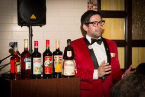 Nick Korn, Italian Spirit Specialist, next to the Campari America portfolio during the Spirited Dinner.