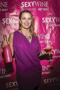 SEXY Wine's U.S. importer, Heather S. Delphin, understands firsthand the importance of continued research after her own breast cancer diagnosis and successful treatment. In October, SEXY Red and SEXY Sparkling Rosé were labeled with special breast cancer awareness tags that can be reversed and used as privacy door hangers. Delphin is shown here at the 2013 Sun WineFest.