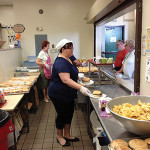 Lynette Lamberti, Human Resource Coordinator with Tony Lodato, Check-In Driver, preparing sandwiches