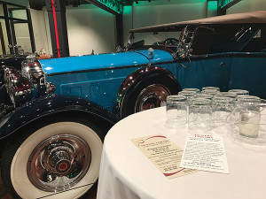 Brass-Era automobiles and motorcycles amidst spirit displays welcomed guests.