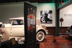 Macallan poster beside a Pre-war/Brass-Era car on display during Bourbon & Brass event.