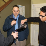 Milton Monzon, Commercial Director of J.C. Imports, pouring wine for David Forte and Richard Lupino of Knights of the Wine Table of Rhode Island.