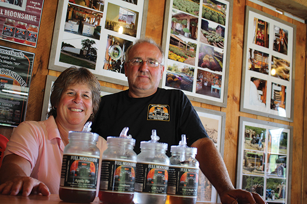 Bill and Lynne Olson along with their lineup of Full Moonshine products. Located behind them are photographs of the Hickory Ledges farm throughout the years.