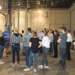 John Taylor (left in blue), Co-owner of Waypoint Spirits, leading a tour of the distillery for CRA and industry members during the CRA Spring Potluck event.