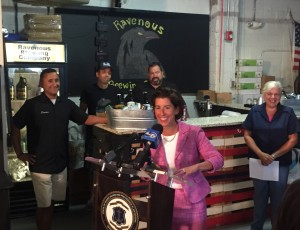 Gov. Gina M. Raimondo at the signing ceremony on September 10 at Ravenous Brewing Company in Woonsocket. The new law allows breweries and distilleries to sell limited amounts of their products to visitors for sampling and off-site consumption.