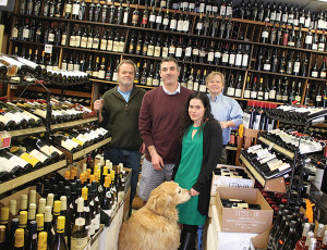 Rob Vickers, Co-Owner; Mike Paradis, Store Manager; Elizabeth Moniz, Store Employee; and Mike Vickers, Co-Owner. Rocky the retriever is the foreground.