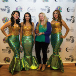 """Mermaid models with Nadine Gengras, Account Development Specialist - Spirits, Connecticut Distributors, Inc., at the """"selfie station."""" Gengras organized Sugar Island Rum's participation in the event."""