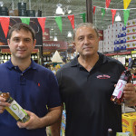 George Mitas, Purchasing and Sales Manager, Mina Distributors, holding Muses Estate White Dry; Dimos Mitas, Owner, Mina Distributors, holding Muses Estate Rose Dry.