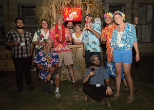 First row standing: Zach Davis, Visitors Center Staff; Derek Luke, Co-Founder and Brewmaster; Brent Ryan (pink Hawaiian shirt and bucket hat): Co-Founder and Master Distiller; two Tiki Hut volunteers; Jason Tsangarides, Brewer; Joe Welch, Rhode Island Sales Representative; and Clare Simpson-Daniel, PR & Events Coordinator. Second row: Pete Lanouette, Brewer and Distiller and Riley Mello, Visitors Center Manager, all with Coastal Extreme Brewing Company.
