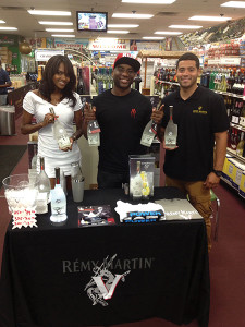 Shown with a Remy V model are Charlamagne tha God and Giancarlo Cowan, Multi-Cultural Key Account Manager, Brescome Barton at Bridgeport's Price Break Liquors.