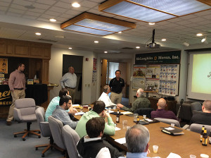 Charlie Paulette presents to members of the McLaughlin & Moran team as Derrick Ransford and Ed Mangine look on.