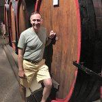 Julius Angelini next to a grappa di Prosecco barrel at the Carpenè Malvolti estate. Carpenè Malvolti ages some of their grappa in large barrels, often seen used when aging wine.