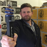 "James McFillin, founder of War Flag Brewing Company, holds the War Flag tap handle, designed to reflect his passion for ""prominent American symbols against tyranny."" McFillin chose to name his company after the American Revolutionary War's Gadsden Flag, which was also the inspiration for the company logo depicting a snake and a barrel. The company supports The Wounded Warrior Project."