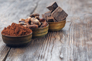 Dark chocolate pieces, cocoa powder and cocoa beans on a wooden