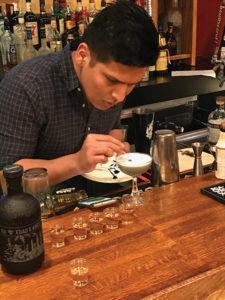 Angel Pena-Fernadez adding garnish to his cocktail creation.