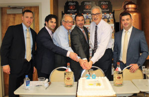 Matthew Malloy, CT Area On-Premise Manager, Tito's Handmade Vodka; David Rosenberg, Vice President, Hartley & Parker; Paul Angelico, General Manager, Hartley & Parker; Frank LaTorra, RI and CT State Manager, Tito's Handmade Vodka; Jerry Rosenberg, President, Hartley & Parker; Anthony Antonecchia, Sales Manager, Hartley & Parker, cutting the cake during the Tito's 20th anniversary celebration.