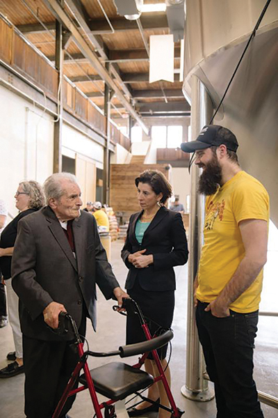 Former Narragansett Brewing Company employee Joseph Ianaire, who worked at the company for 34 years, next to Gov. Gina M. Raimondo during a tour of the Isle Brewers Guild facility in May. Isle Brewers Guild is now home to Narraganset Beer's brewing operations.