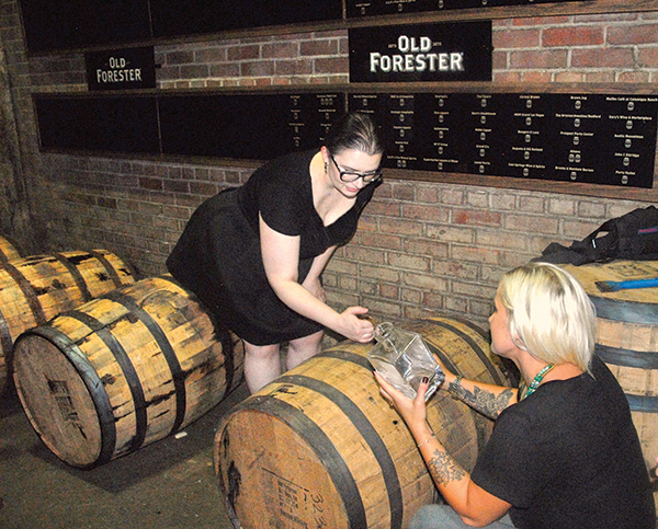 Lauren Hansen, Bartender and Supervisor, J. Timothy's Taverne, pulling a bourbon sample from one of the Old Forester bourbon barrels.