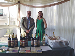 Mike Dudeff and Jillian Simms of Cellar Fine Wines prepare to pour Tuscan Sun Wines at May's Notre Dame High School  fundraiser.