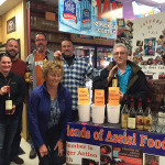 Five out of the six customers who won the raffle for a chance to purchase the elusive whiskies, and kneeling in front is Molly Newton, of Friends of Assisi Food Pantry, who led the raffle drawing.
