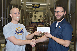 Ted Pert, Tasting Room Manager, Two Roads Brewing Co. with Chris Soltis, Curator, Connecticut Air and Space Center at the brewery on February 15, 2016.